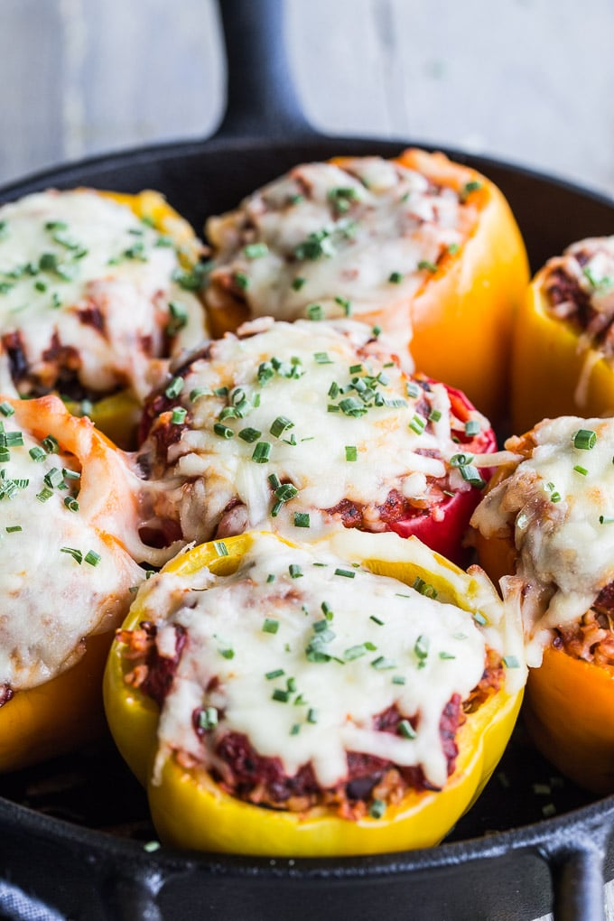 Side view of Vegetarian Stuffed Peppers in a black cast iron pan.