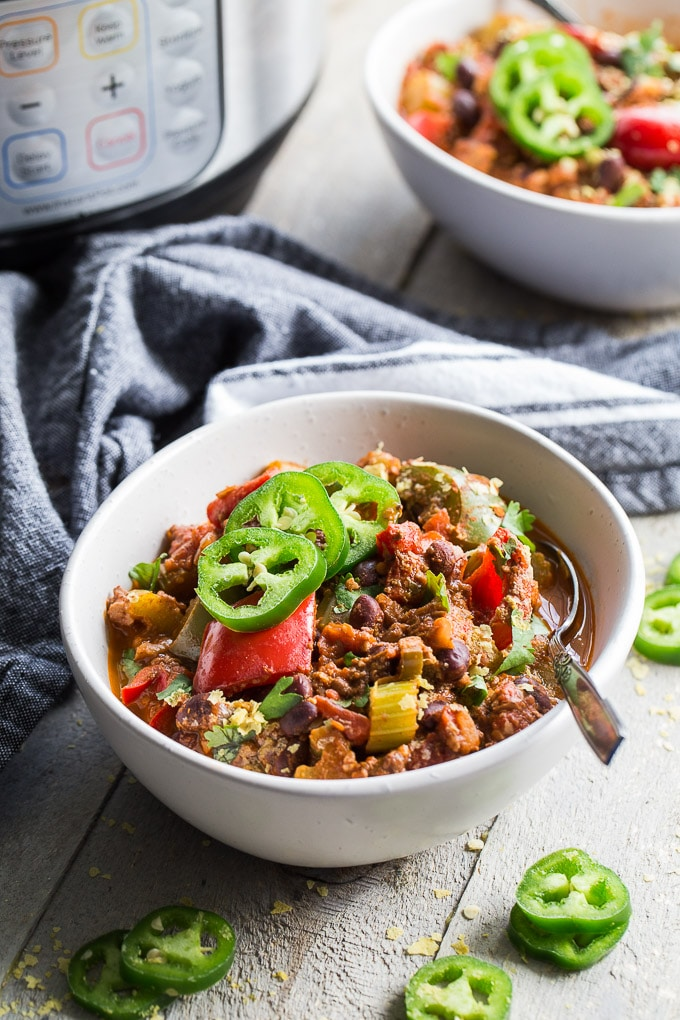 Up-close side view of Instant Pot Spicy Vegan Chili in a white bowl on a wooden surface with the Instant Pot and another bowl of chili in the background.
