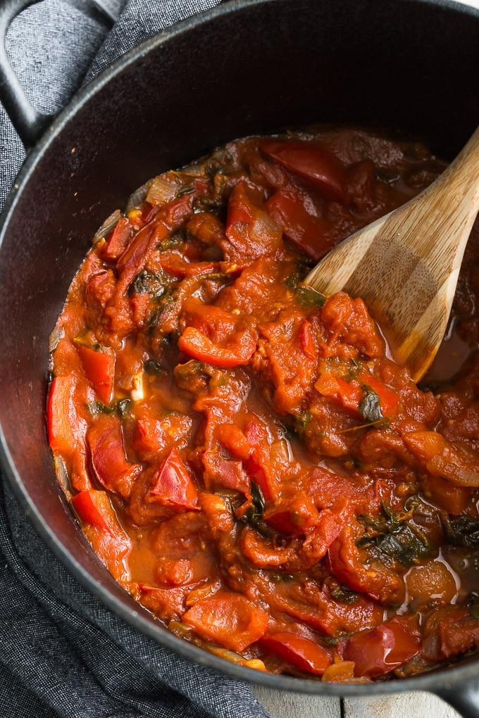 Overhead view of Tomato Basil Marinara Sauce ingredients stewed together in a black cast iron pot.