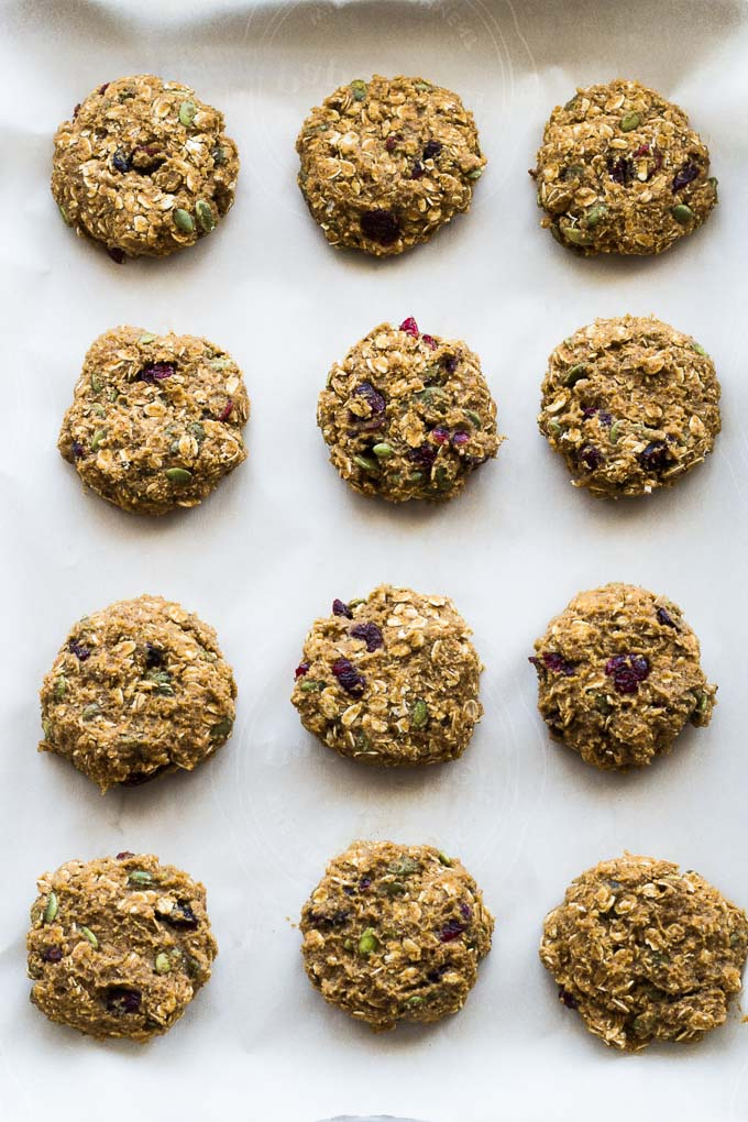 Overhead view of Avocado Pumpkin Oatmeal Breakfast Cookies arranged on a baking sheet lined with parchment paper.