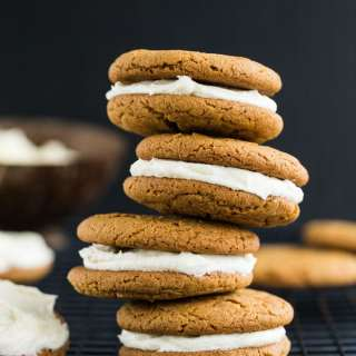 Side view of four Chewy Ginger Cookies with Lemon Cream Cheese Frosting stacked on top of each other.