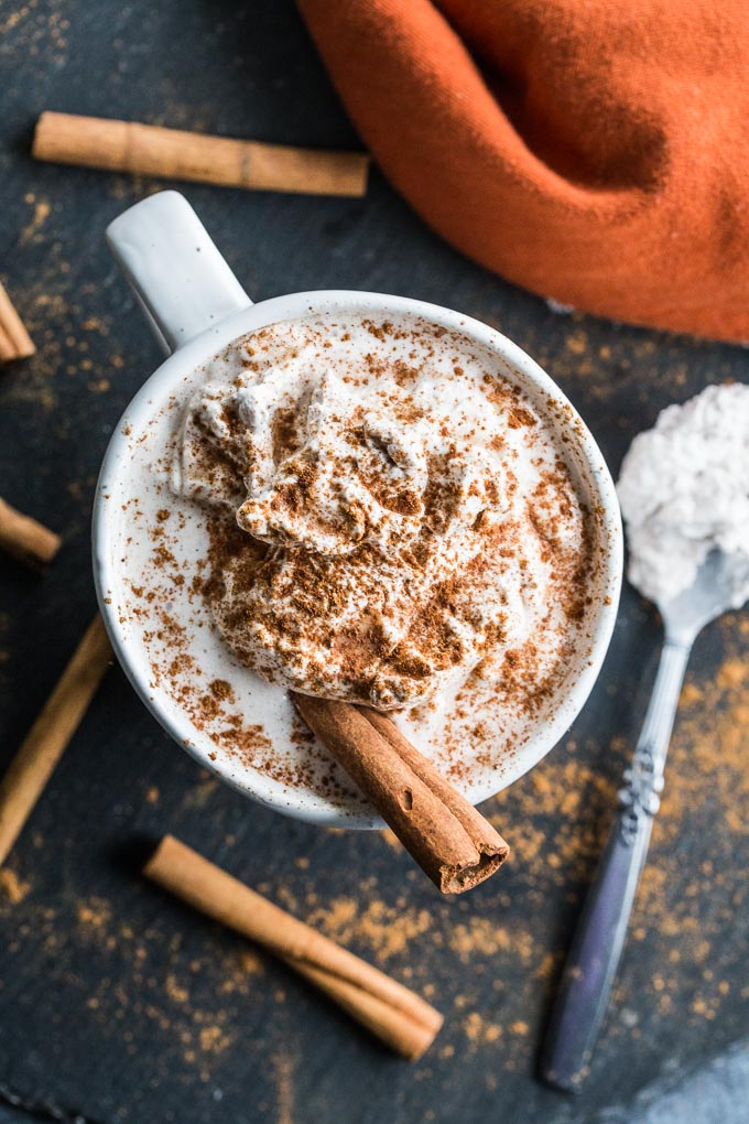 Overhead view of a Pumpkin Spice Collagen Latte on a dark surface surrounded by cinnamons sticks.