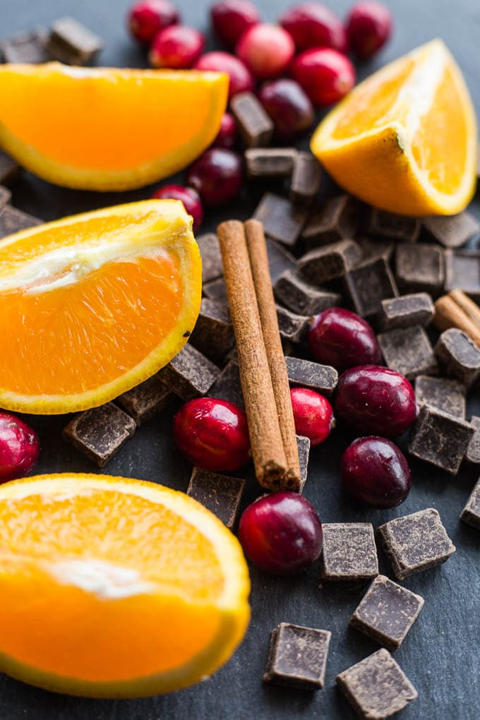 Orange slices, cranberries, chocolate chunks and cinnamon sticks arranged on a dark surface.