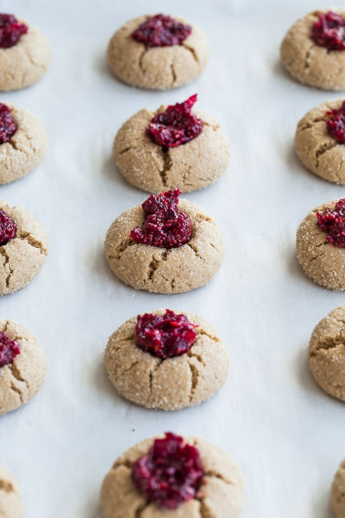 Cranberry Orange Thumbprint Cookies on a baking sheet and filled with cranberry orange filling.
