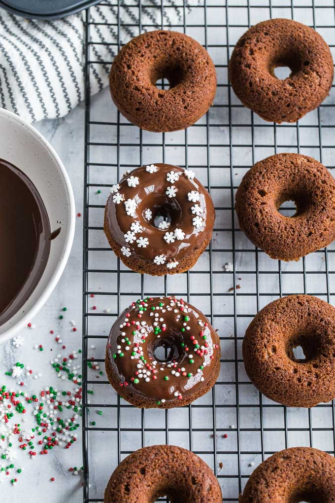 Overhead view of Gingerbread Protein Donuts being dipped in chocolate glaze and decorated with sprinkles.