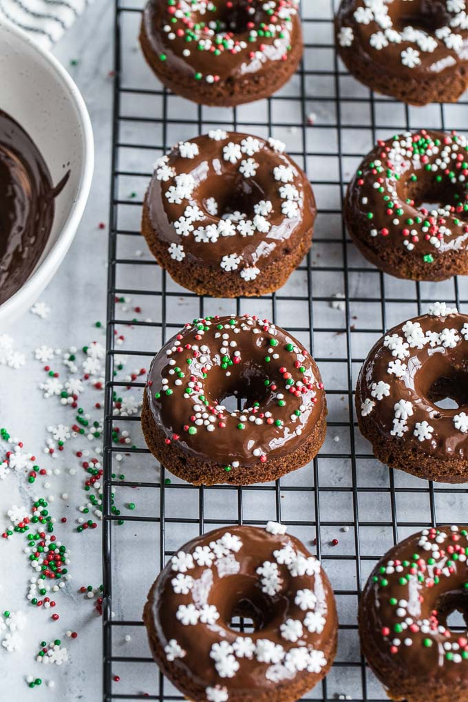 Overhead view of Mini Gingerbread Protein Donuts with Chocolate Glaze on a wire rack.
