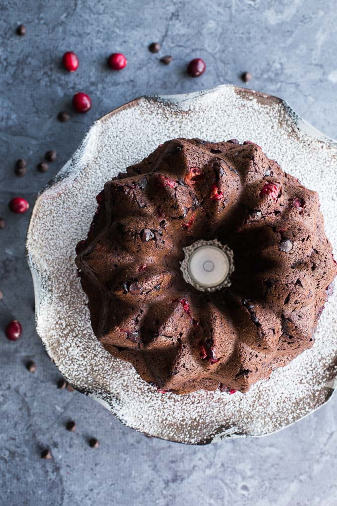 Overhead view of Dark Chocolate Cranberry Bundt Cake on a cake stand.