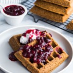 Two Gingerbread Waffles with Partridgeberry Compote on a grey plate, with a stack of waffles in the background.