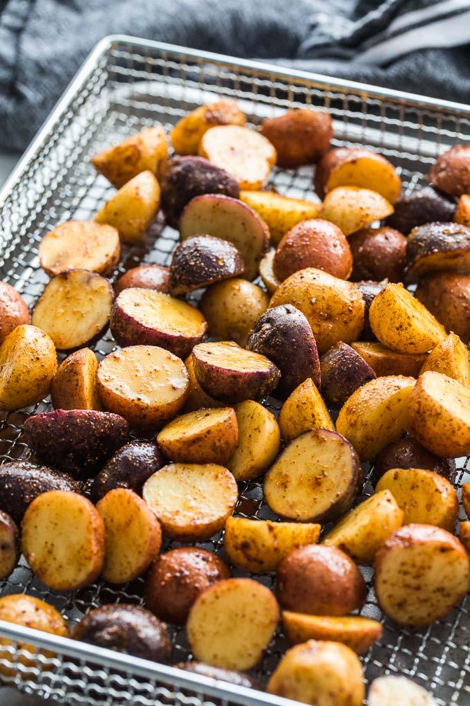 Seasoned baby potatoes arranged in the air fryer basket.