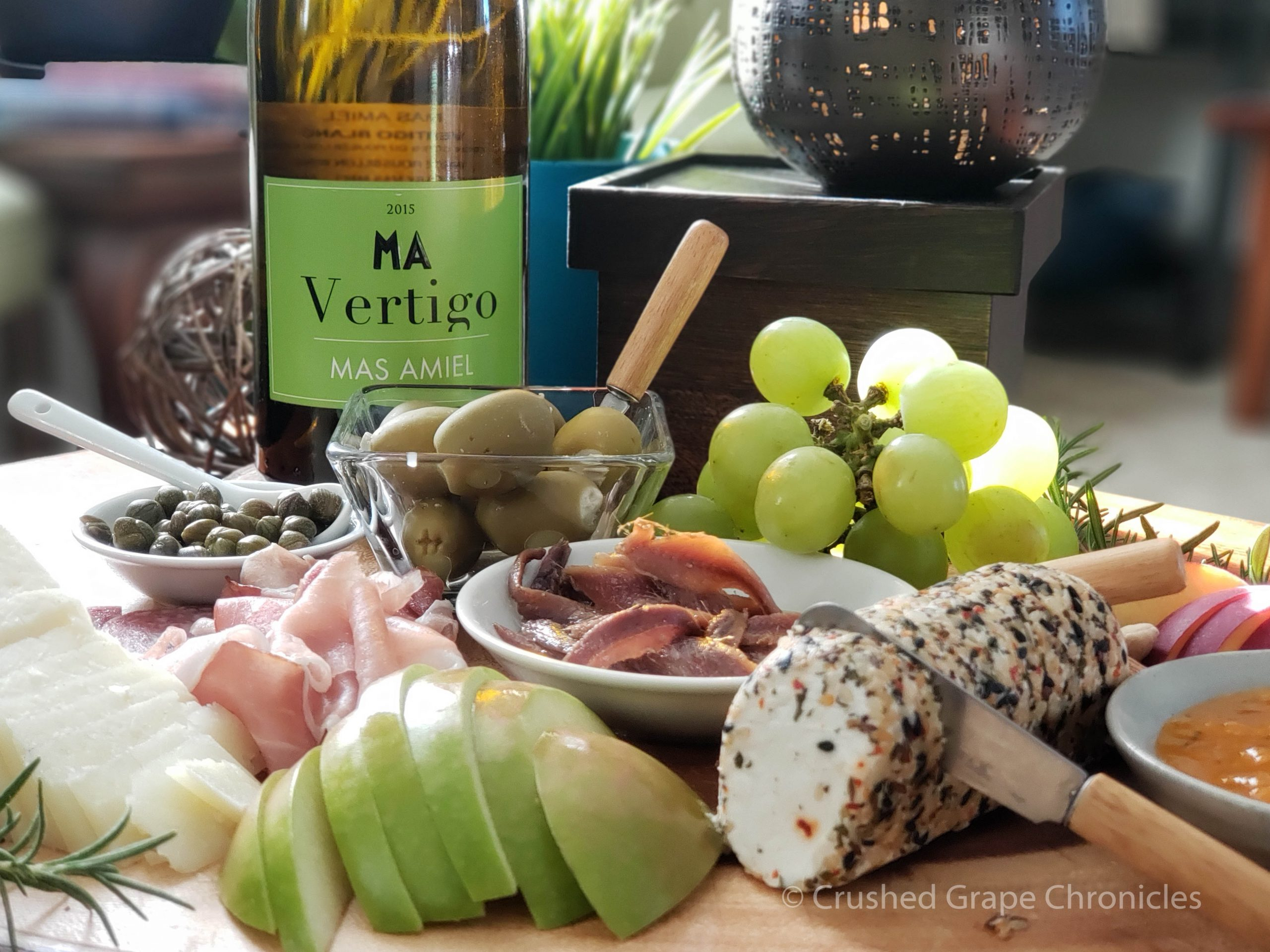 Mas Amiel 2015 Vertigo with a platter of olives, capers, apple, manchego, goat cheese with herbs and spices, nectarine, grapes, and anchovies.