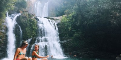 2 girls sitting in front of waterfall