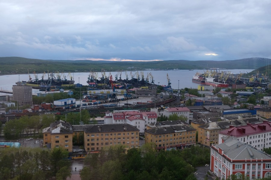 Large piles of coal sit waiting to be loaded onto ships in the Port of Murmansk.