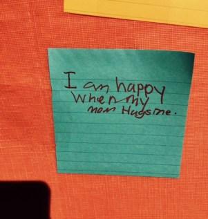 """Green Post-it on orange board reads, """"I am happy when my Mom hugs me."""""""