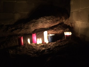On a rock ledge in the dark cave are eight candles of various sizes--all are lit except the two red ones that have a small white candle between it.