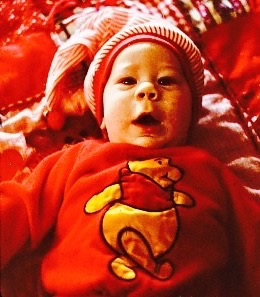 Baby boy in a red, Winnie the Pooh sweatshirt, also wears a candy cane stripe cap. He lies on a red plaid blanket and has a look of wonder on his face.