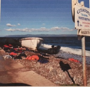 A small boat rests on a Greek shoreline surrounded by discarded orange vests and other debris.