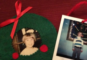 Two homemade Christmas ornaments with red ribbon show a little smiling girl encircled by a green felt wreath and a Polaroid photo of a little boy standing in front of Christmas ornaments.