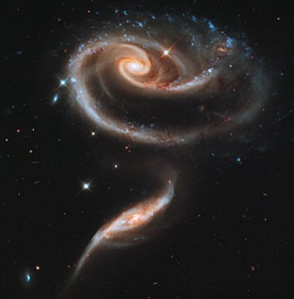 A large spiral twists in the darkness with lights of blue, white and red.