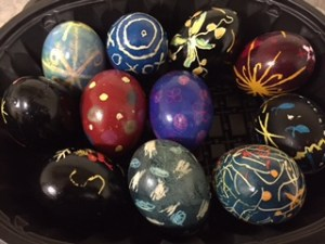 Here is a bowl full of Pysanky eggs done by children. Several are polka dots and x's and o's.