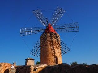 Spanish rust-colored stone windmill with six black, metal arms and a red cone top sets in middle of photo with a blue sky behind it.