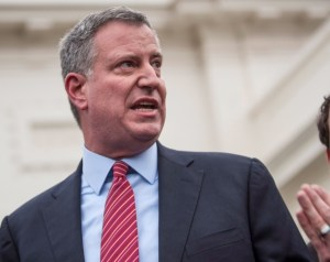 NYC May Bill de Blasio is looking left with one hand up, and his mouth open like he is speaking. He has salt and pepper hair, is tall and stocky, and wears a dark blue suit, light blue shirt and red and white striped tie.