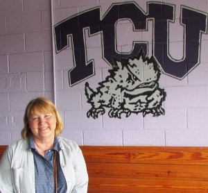 C.S. Boyll, blonde hair, round, smiling face, stands in front of a TCU logo with the cartoon of a fighting horned frog