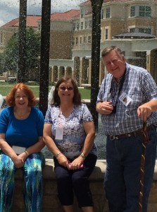 Two women sit and a man stands next to them at TCU Frog Fountain.