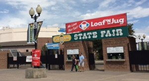 "Entrance to Colorado State Fair includes a green sign with white letters that say, ""State Fair,"" and a red and white sign above it that advertises Loaf 'N Jug in red and white. There is a couple leaving the brick entrance flanked by two ticket windows and a large old fashioned lamp post."