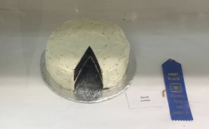 Blue ribbon is beside David Jordan's tag and his chocolate cake with white frosting set on a silver foil circle. A slice has been cut out so the judges could see the even two layered cake.