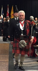 A somber kilted gentleman leads the haggis march.