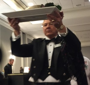 "Server carries honored guest ""haggis."""