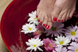 A red bowl holds water with white and pink daisies floating in it. Red painted toe nails on two feet are raised above the water.