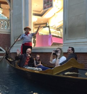 Gondolier stands in boat waving while one grandpa waves, his granddaughter smiles, his daughter takes a photo and her boyfriend laughs. All in the Gondola.