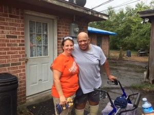 Orange shirt woman stands with older man and his walker, smiling at camera outside his brick home.