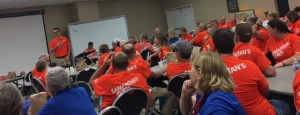 A large group of sitting orange shirt volunteers and two blue shirt volunteers listen to a speaker standing by a white board.