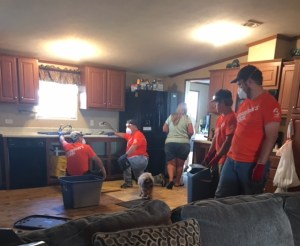 Orange shirted men are kneeling beside a kitchen sink with masked covering their mouths and noses.
