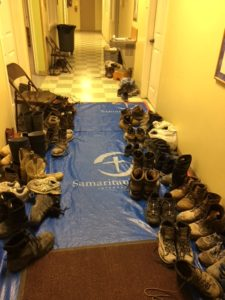 "Hallway shows many different kinds of muddy shoes on both walls with a blue plastic ""Samaritan's Purse"" cover on the floor."