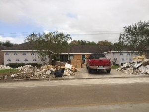 Ranch house has new insulation on its outside, with lots of garbage on the curbs between the red pick-up in the driveway.