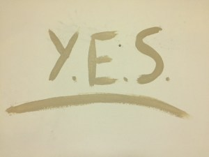 "The tan wall has the word ""Yes"" painted on it in darker tan paint."