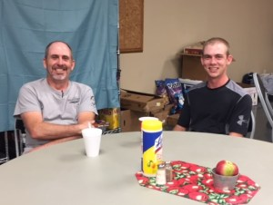 A young man and a middle age man sit at a round table and smile.