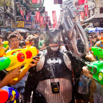 Person in Batman costume being soaked by a crowd of people using water guns