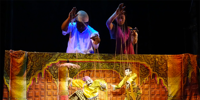 Two people operate marionettes