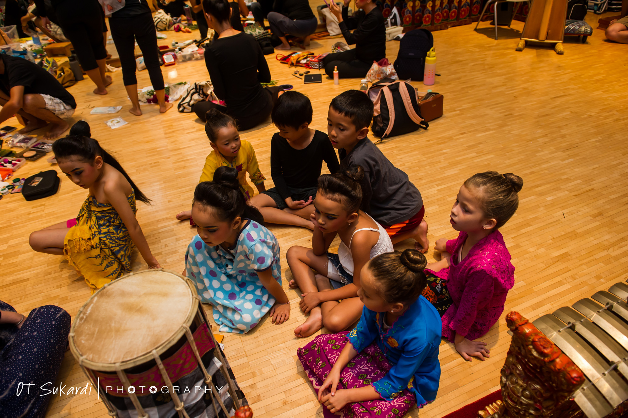 Young performers in street clothes sit on performance floor