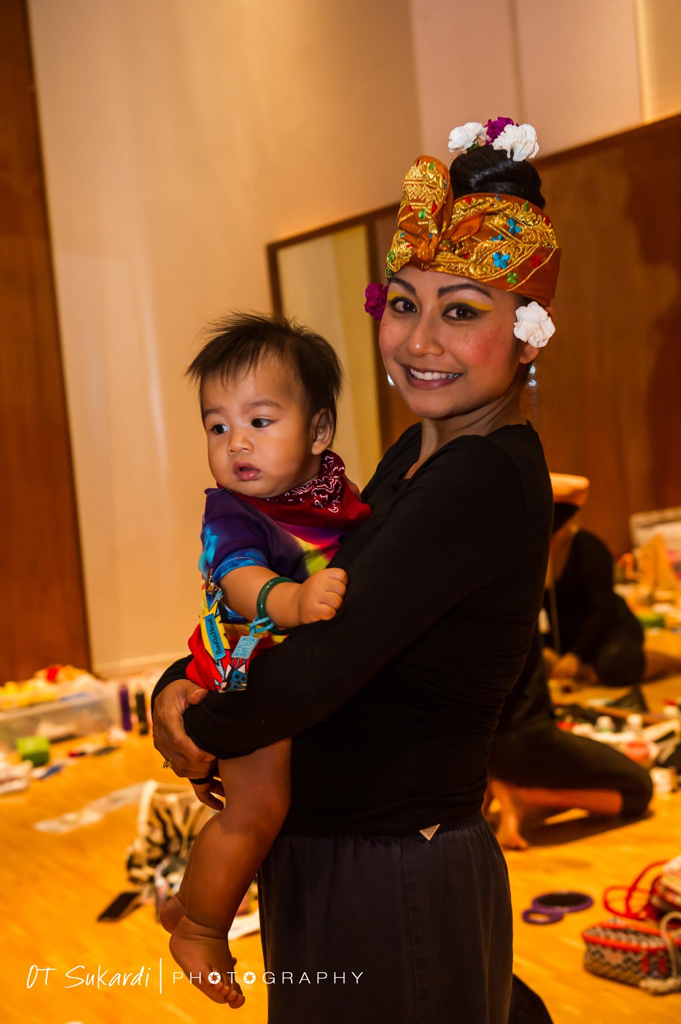 Female performer holds an infant