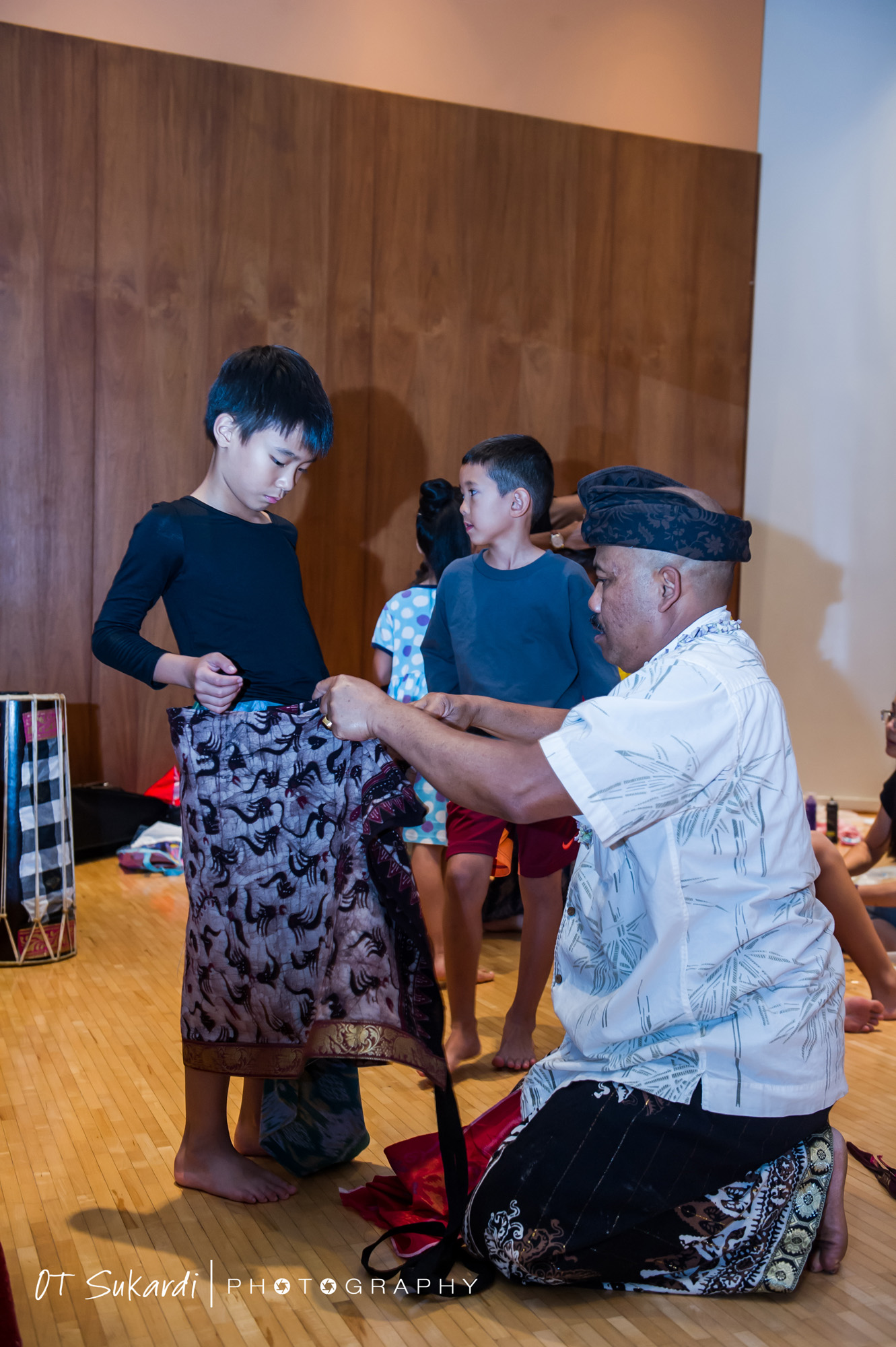 Boy performer being dressed in gray sarong
