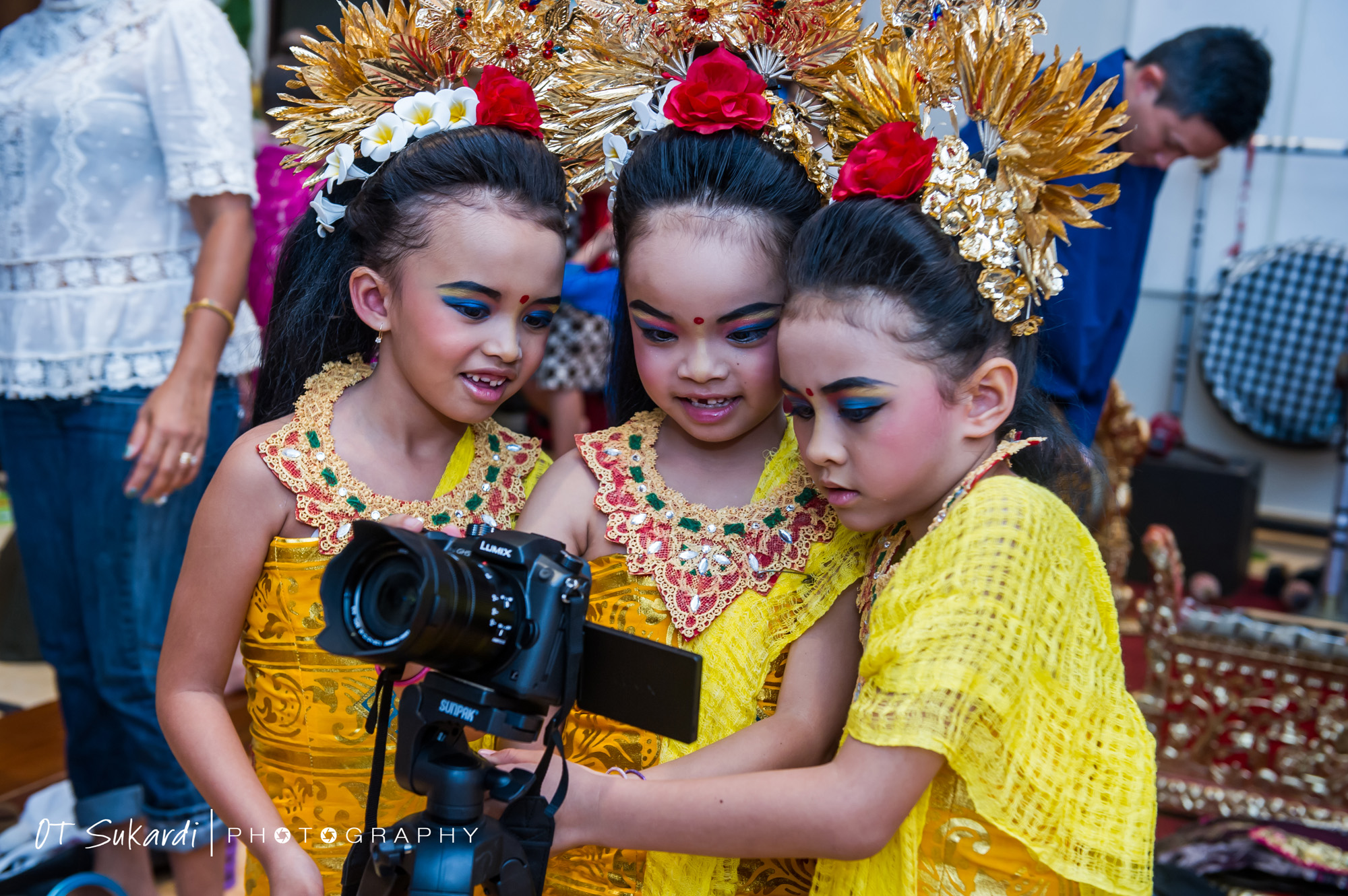 Young girls in costume look at photos on a camera