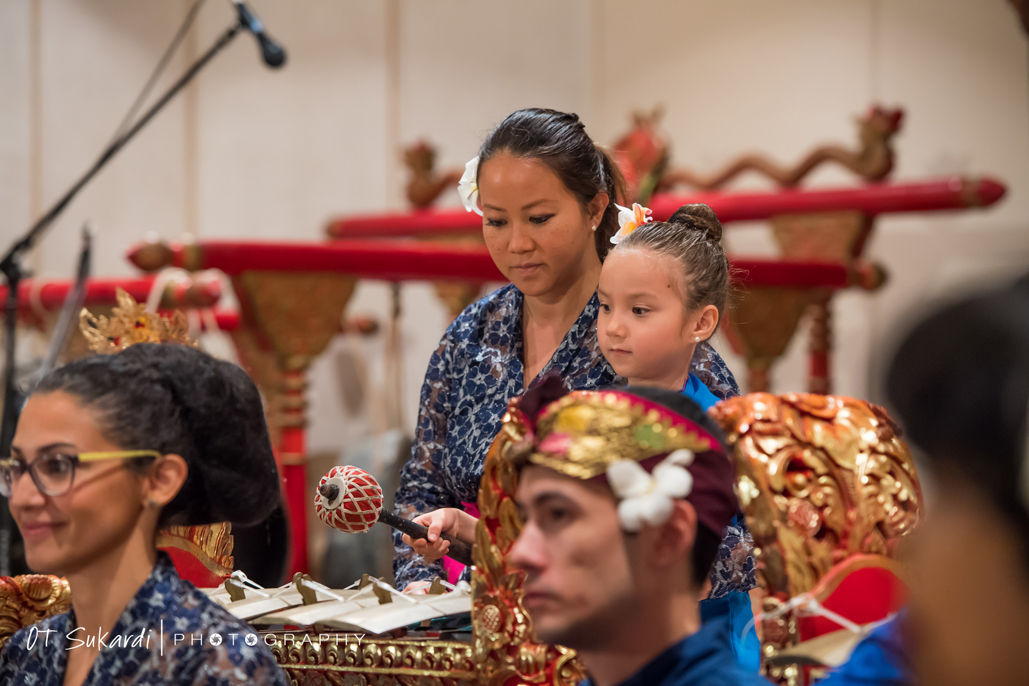 very young girl sits next to woman and plays gamelan keys
