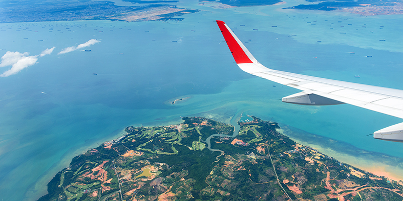 Blue sky, small islands, ocean/sea and a part of airplane engine, top view from an airplane's window