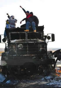 Activists shouting back at law enforcement on top of burned out DAPL truck - photo by C.S. Hagen