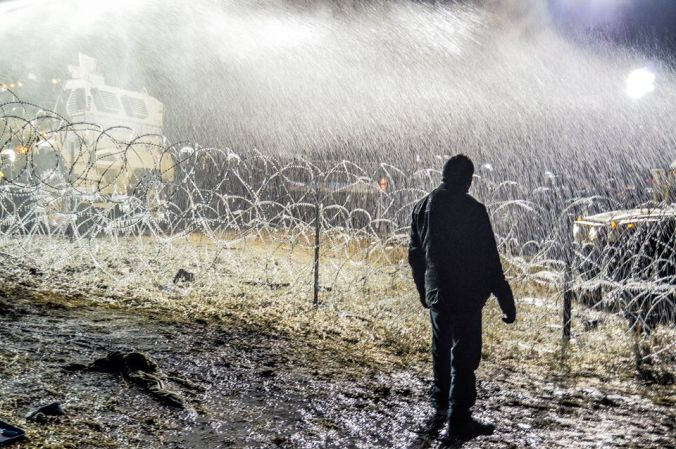 Activist standing under a shower in sub-freezing temperatures - photo by Rob Wilson Photography